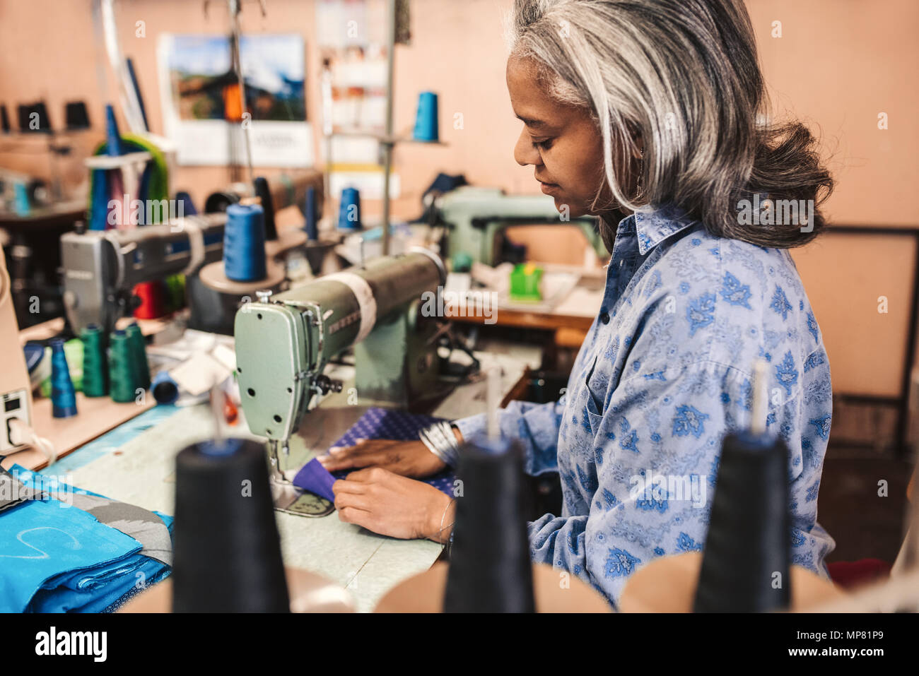 Mature woman sewing cloth in her clothes workshop - Stock Image