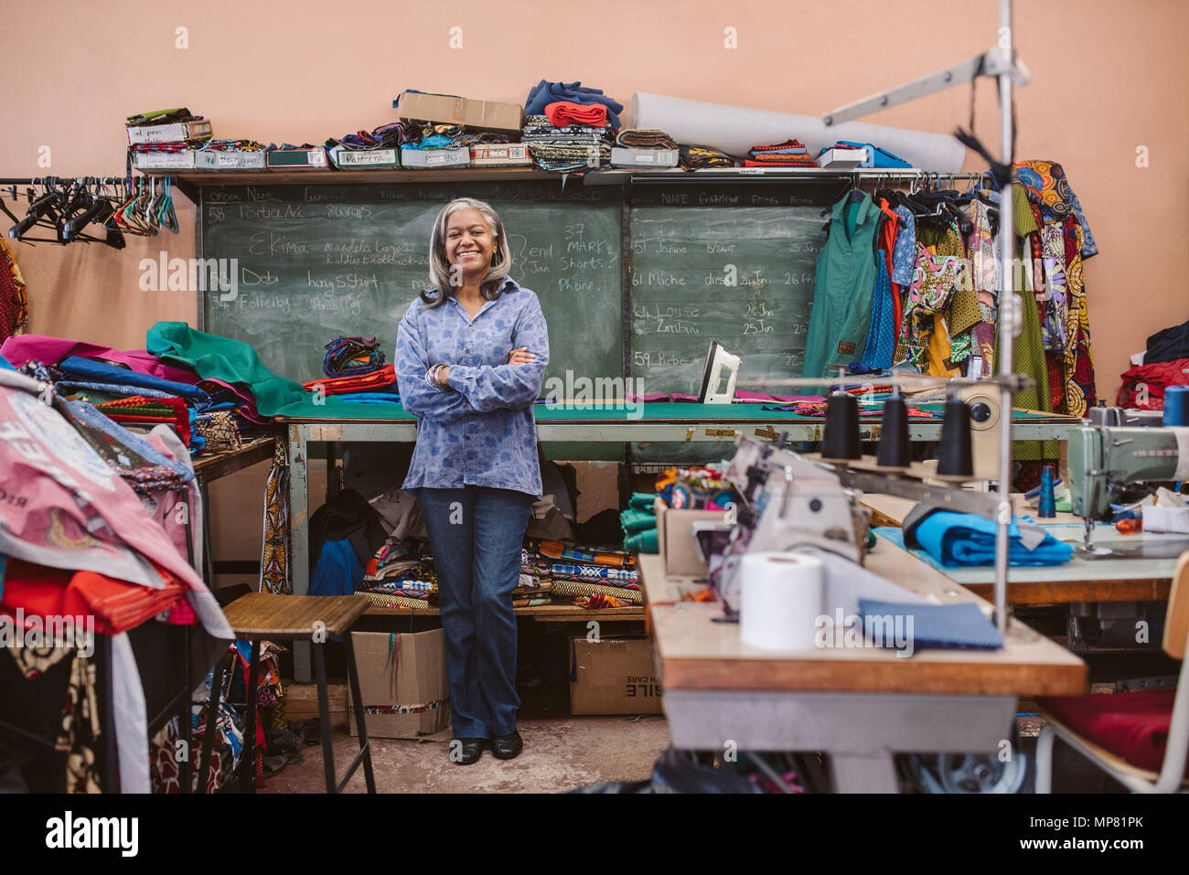 Smiling mature seamstress standing in her busy sewing workshop - Stock Image
