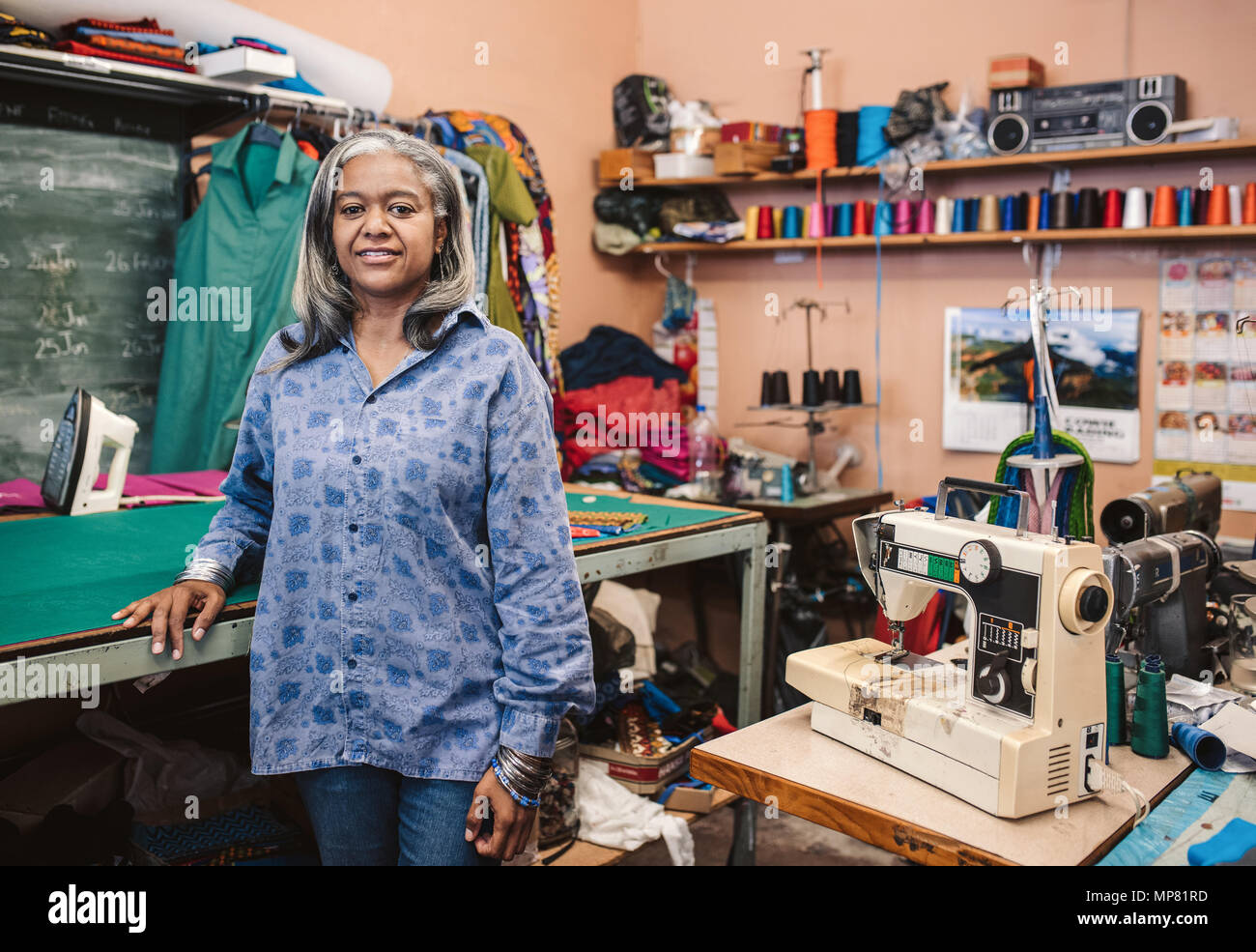Mature seamstress standing by a table in her sewing workshop - Stock Image
