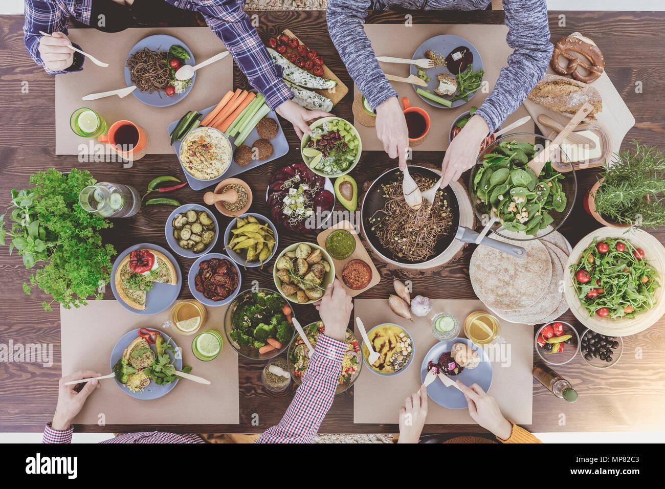People enjoying family dinner at vegetarian restaurant - Stock Image