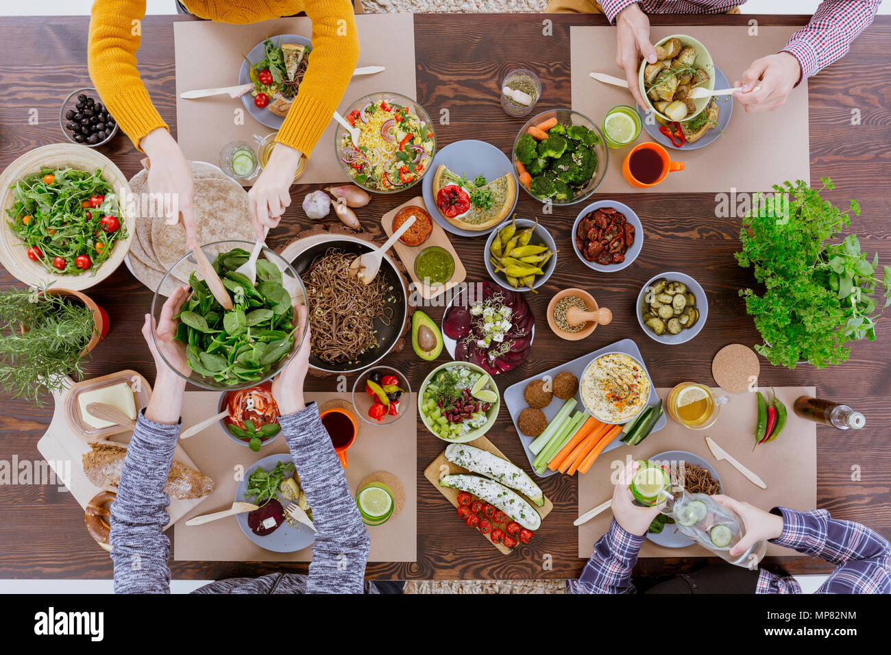 Various vegetarian food lying on rustic wooden table - Stock Image