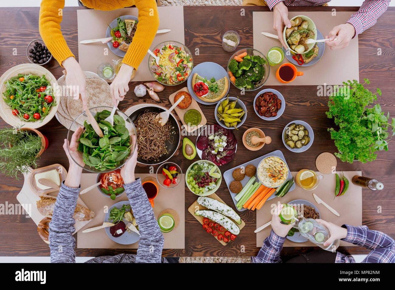 Various vegetarian food lying on rustic wooden table - Stock Image