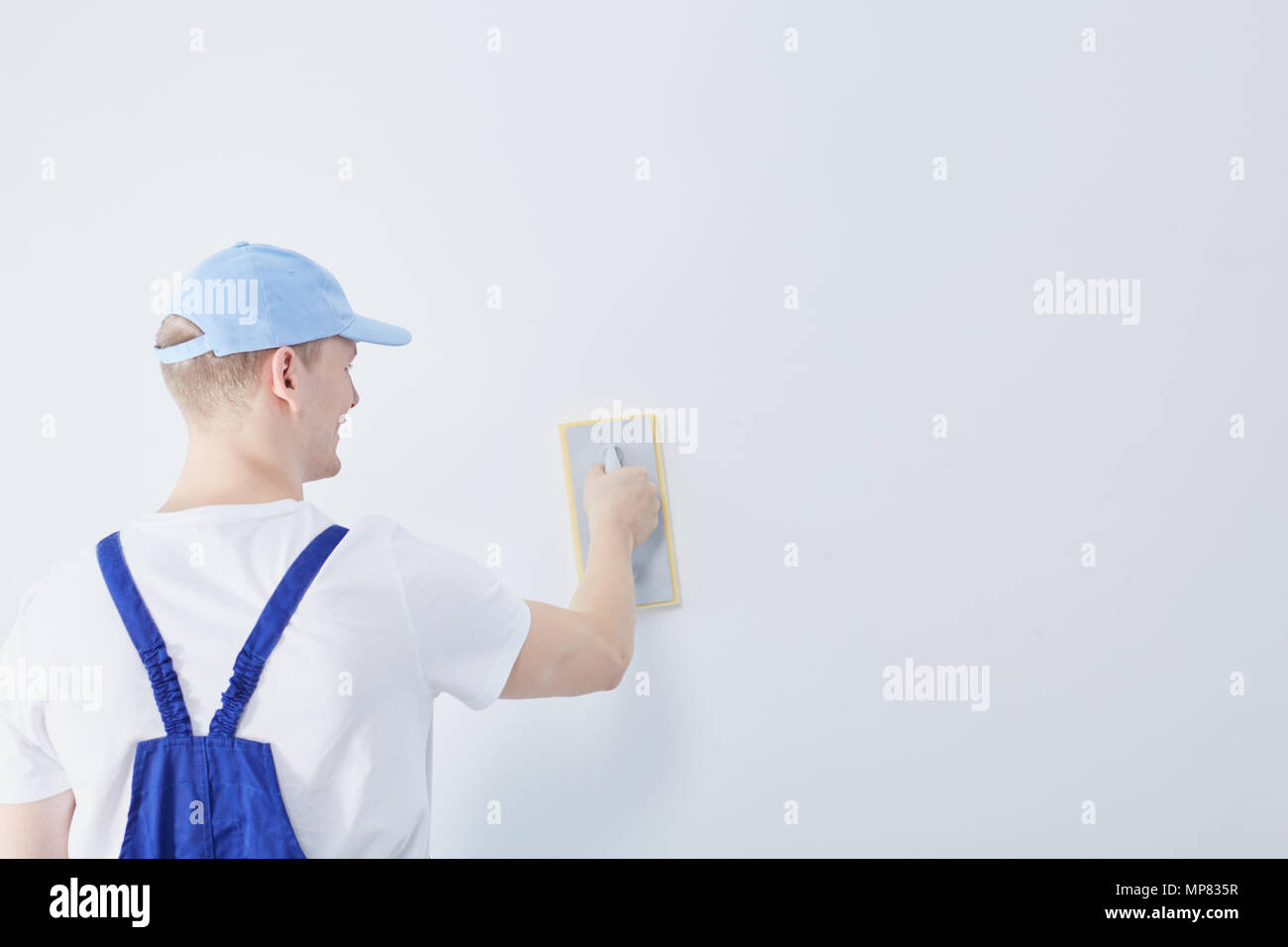 Young construction worker preparing the white wall in the house for painting - Stock Image