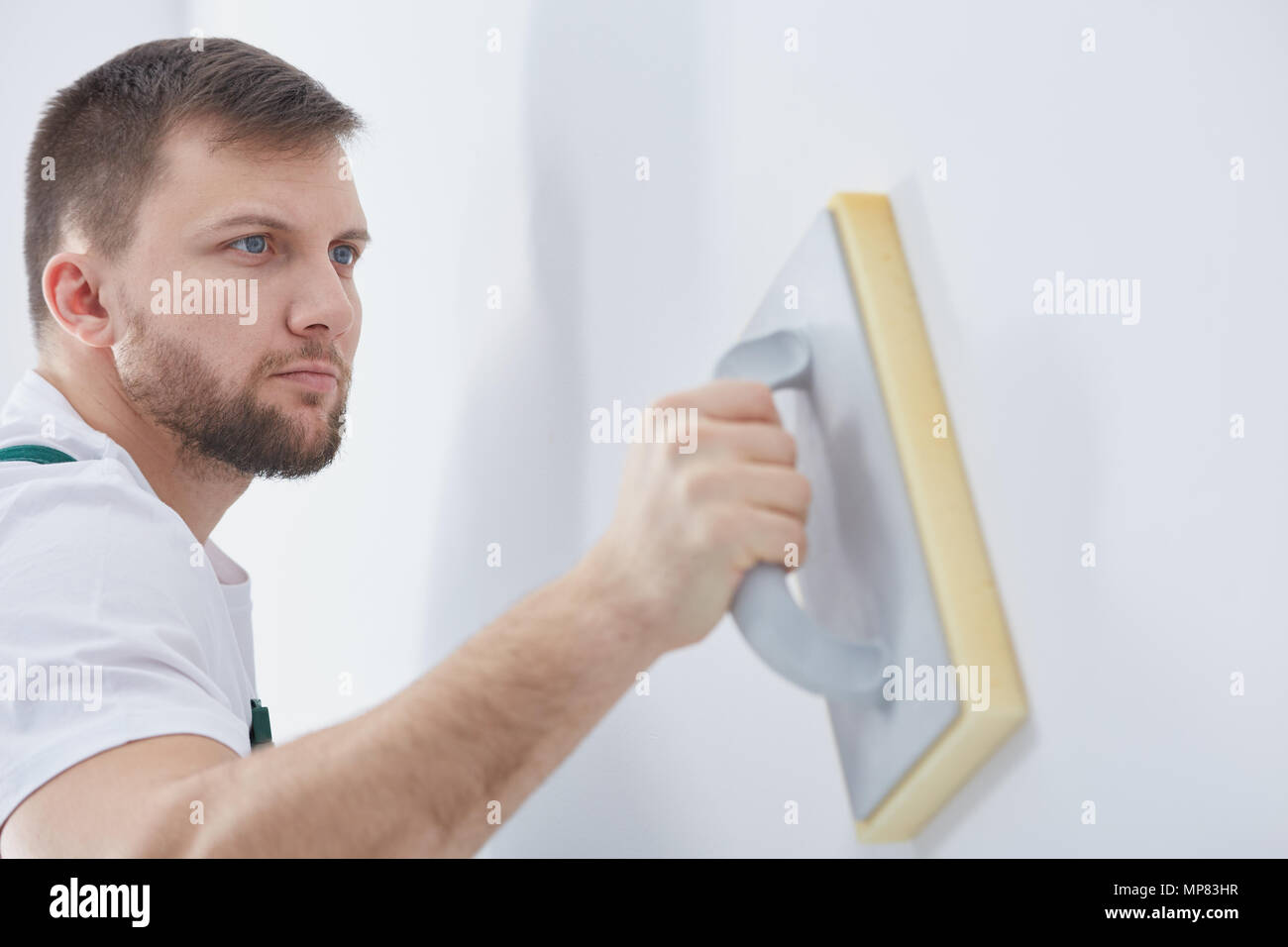 Young specialist rubbing down the wall before painting - Stock Image