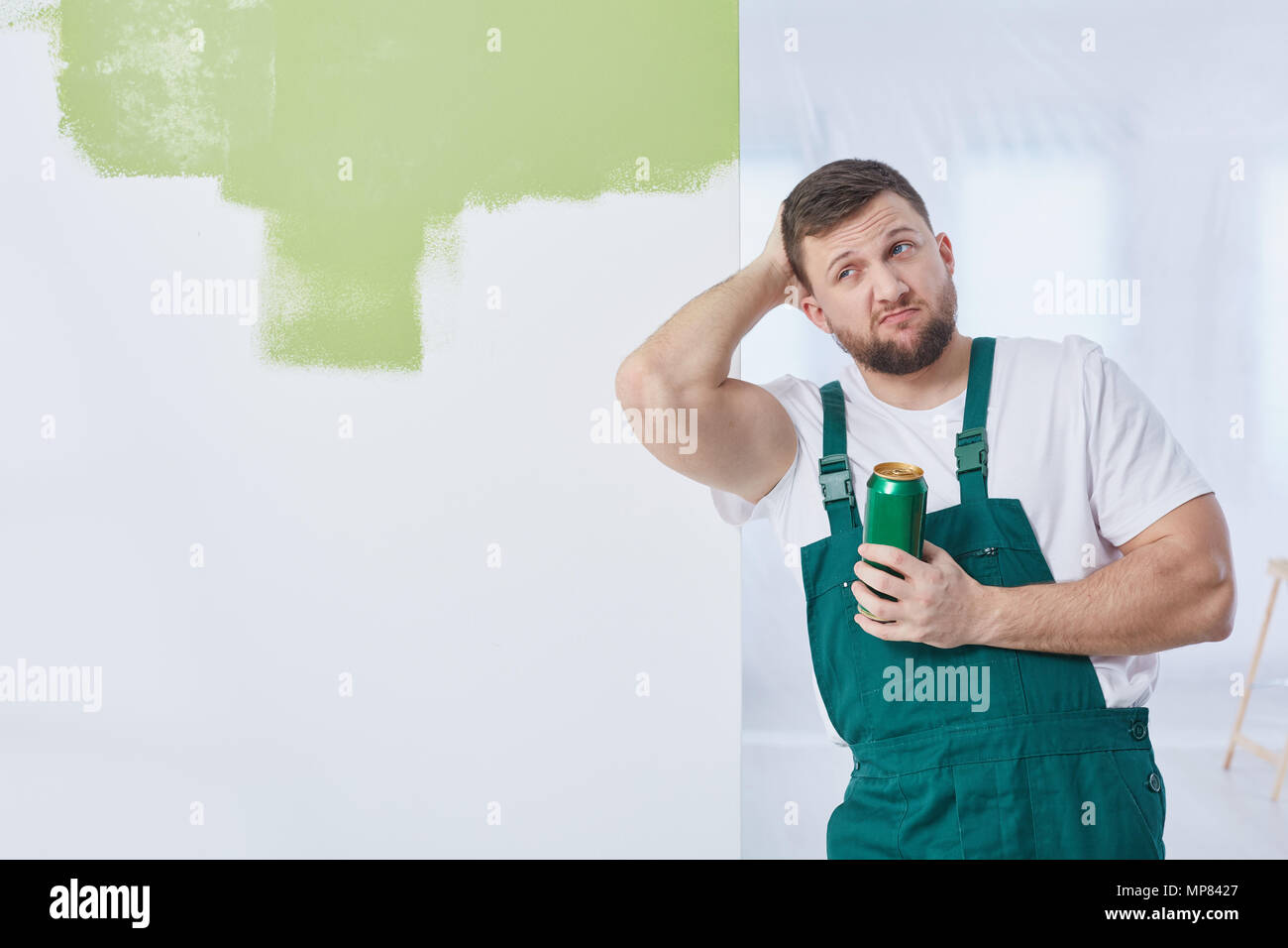 Young  construction worker with beer having break at work - Stock Image