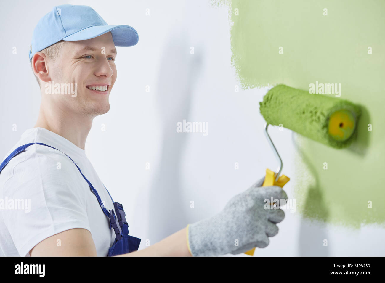 Happy professional interior construction worker painting the wall - Stock Image