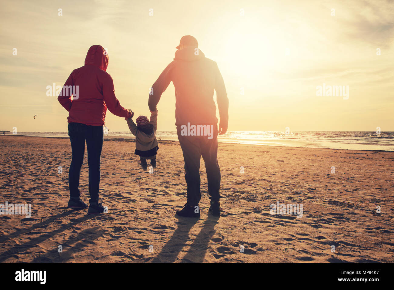mother and father swinging child by the arms on the beach at sunset - Stock Image