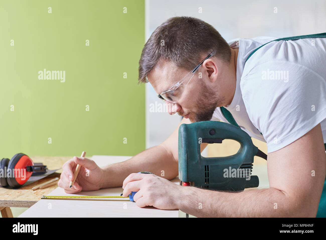 Young handsome specialist drawing plan of home renovation - Stock Image