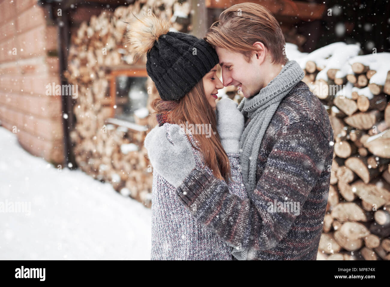 christmas happy couple in love embrace in snowy winter cold forest, copy space, new year party celebration, holiday and vacation, travel, love and relations Stock Photo