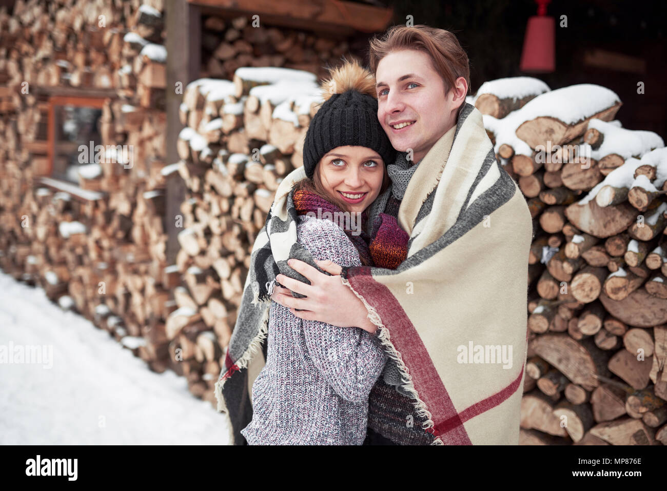 christmas happy couple in love embrace in snowy winter cold forest, copy space, new year party celebration, holiday and vacation, travel, love and relations - Stock Image