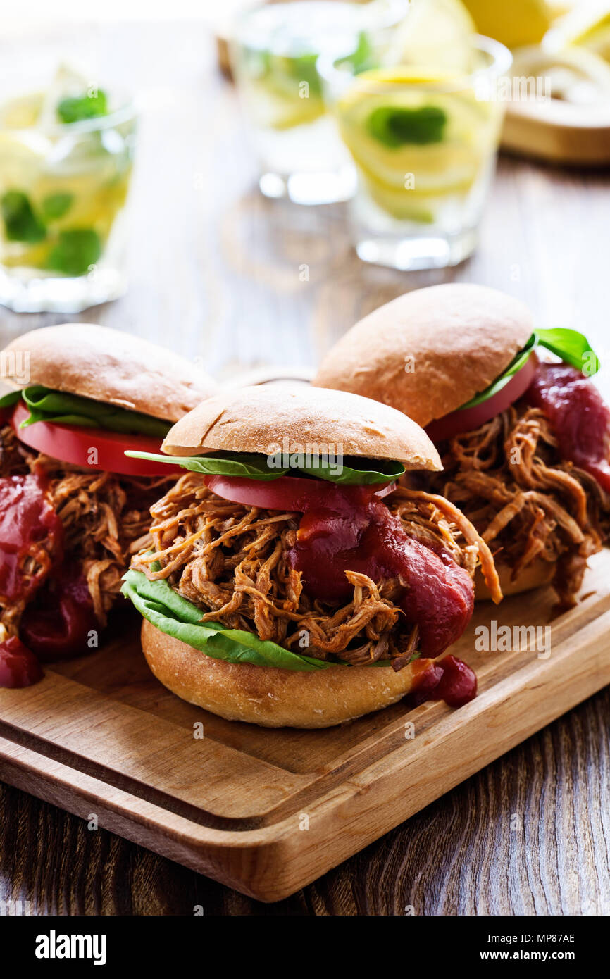 Pulled pork sandwiches with leaf vegetables, tomato on wooden board on picnic table - Stock Image
