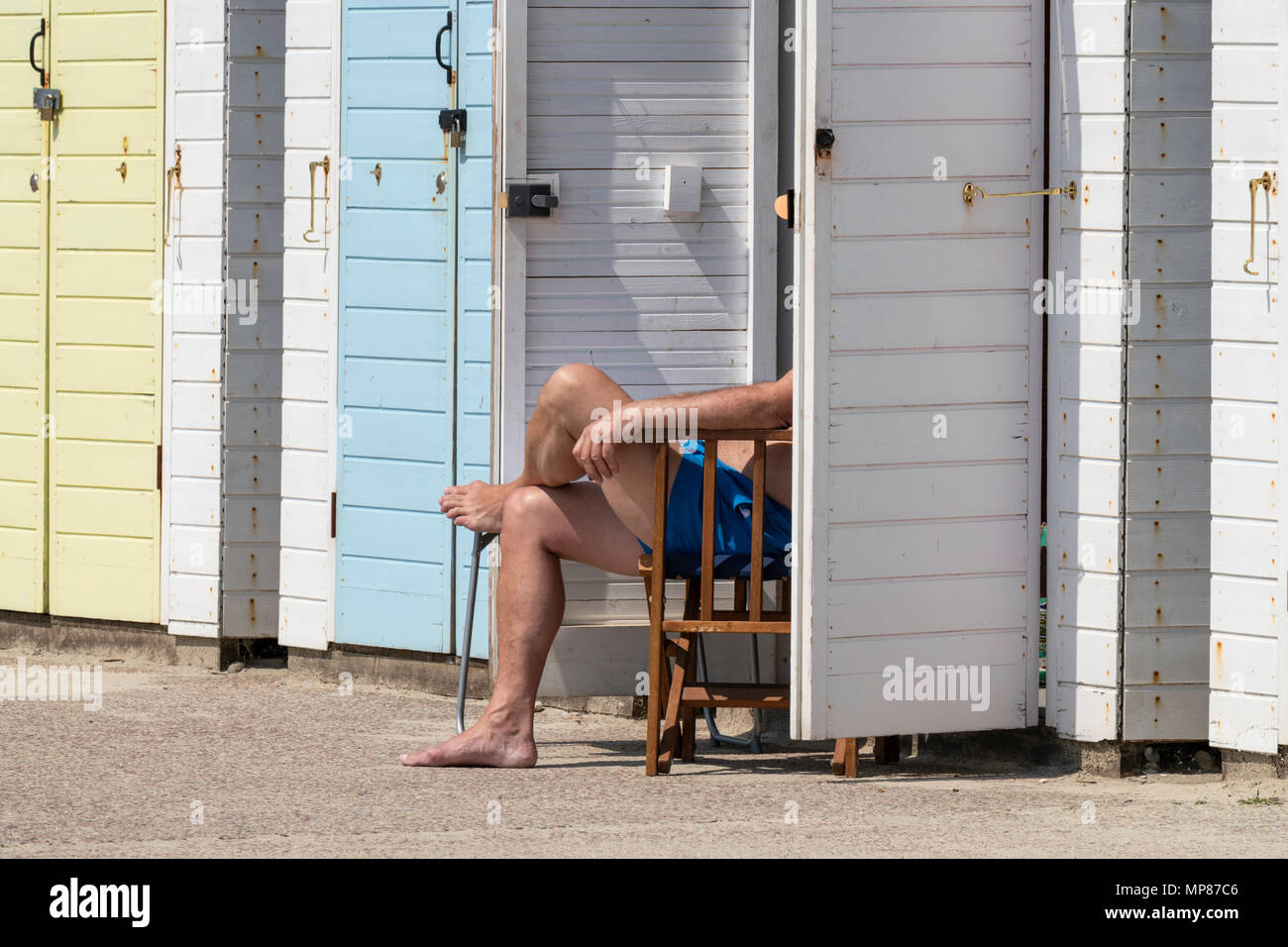 View of unidentifiable man sitting on chair by beach hut Lyme Regis Dorset England UK - Stock Image