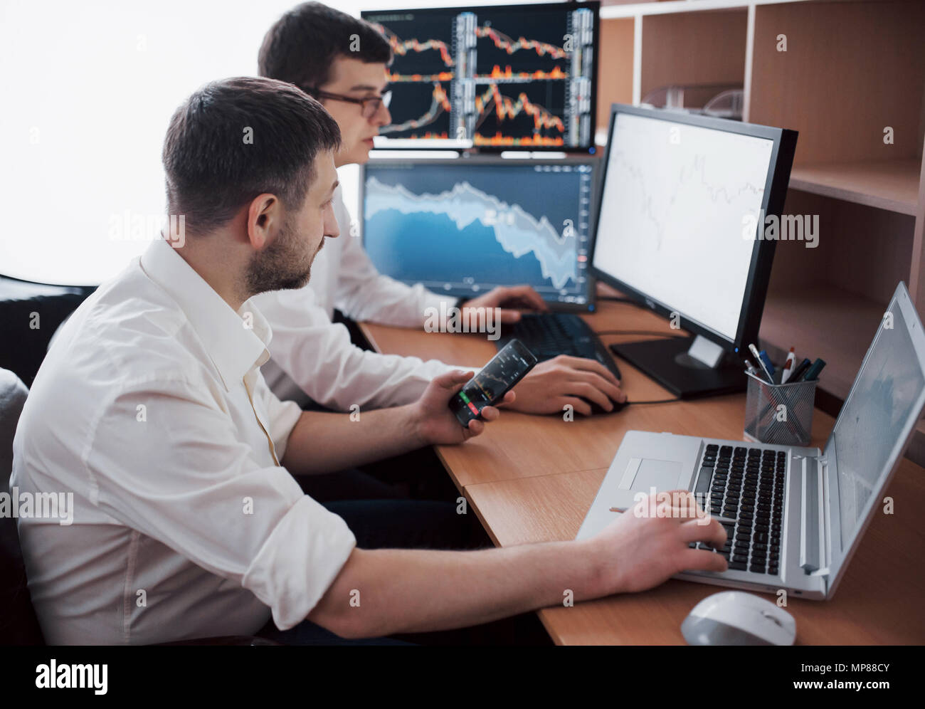 Businessmen trading stocks online. Stock brokers looking at graphs, indexes and numbers on multiple computer screens. Colleagues in discussion in traders office. Business success concept - Stock Image