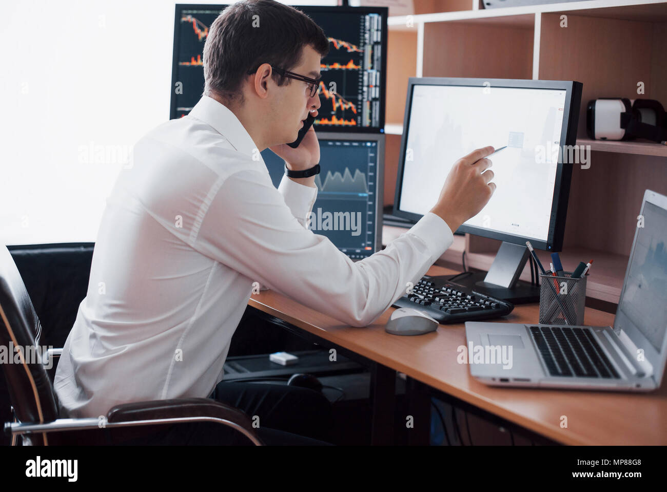 Stockbroker in shirt is working in a monitoring room with display screens. Stock Exchange Trading Forex Finance Graphic Concept. Businessmen trading stocks online - Stock Image