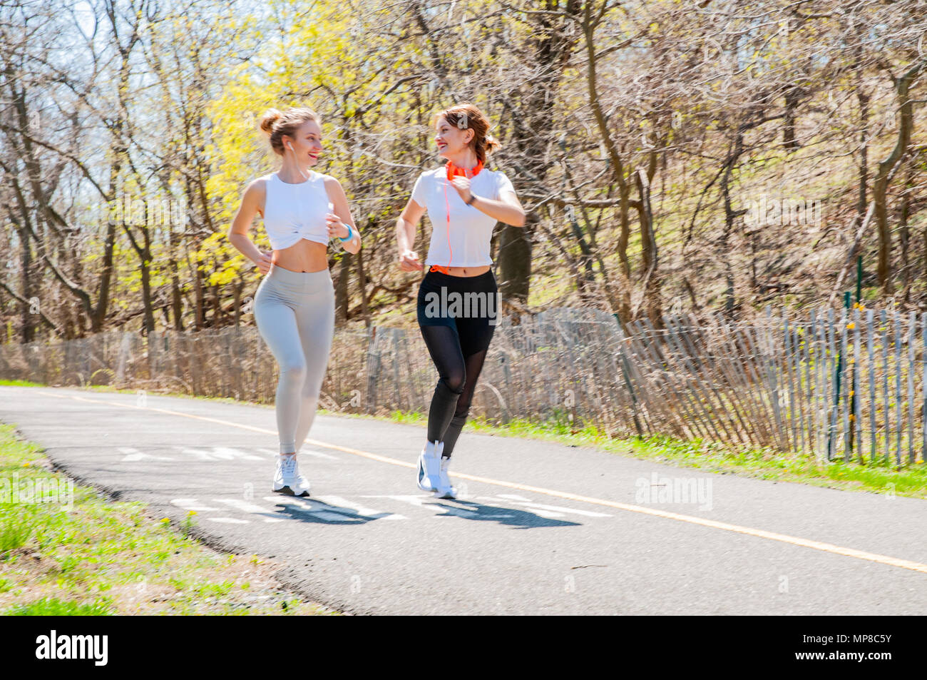 Two happy sporty girls running in the park. Female fitness training outside  Stock Photo - Alamy