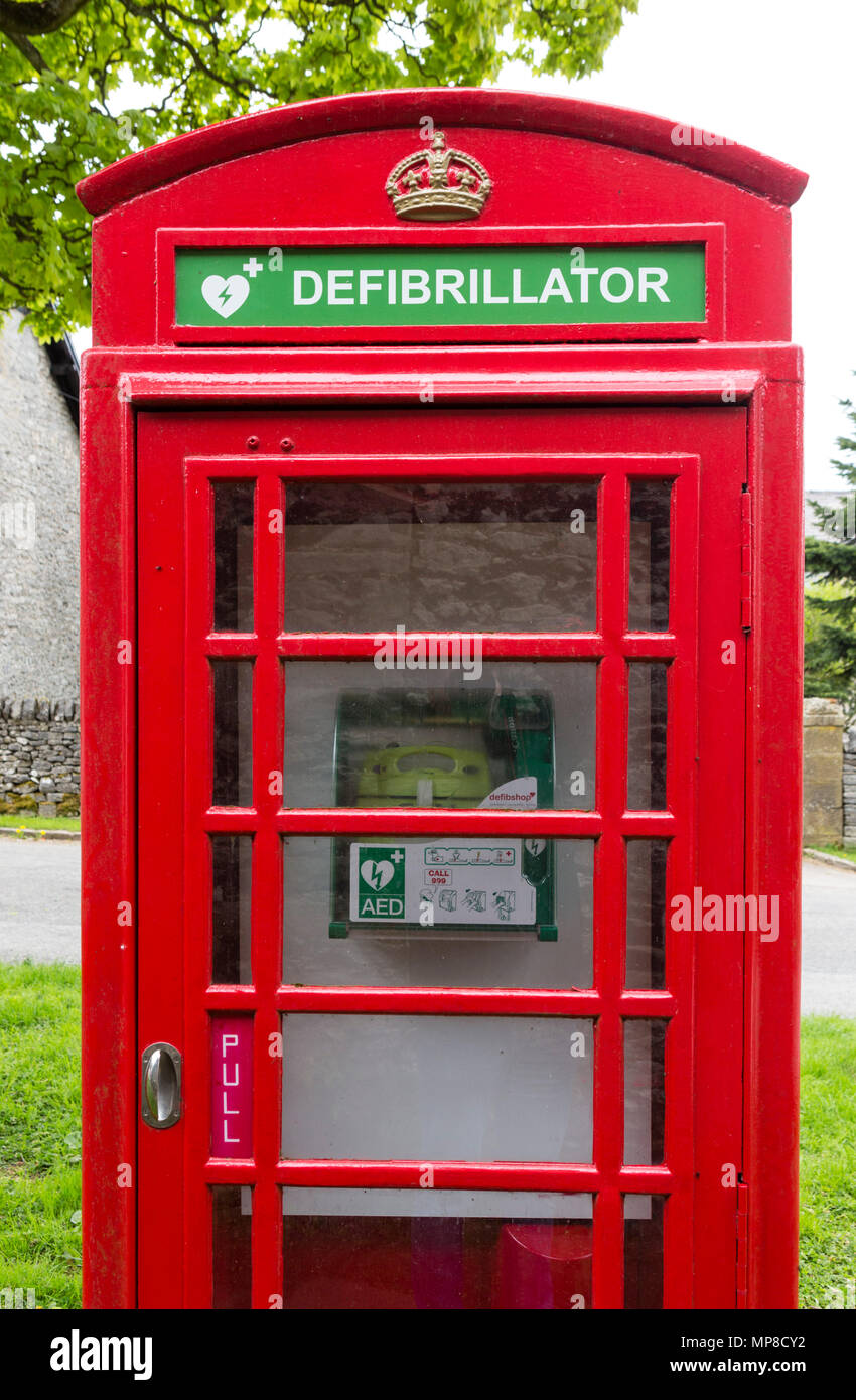 Traditional red telephone box being used to house a public defribillator, Sheldon, Derbyshire, England, UK - Stock Image