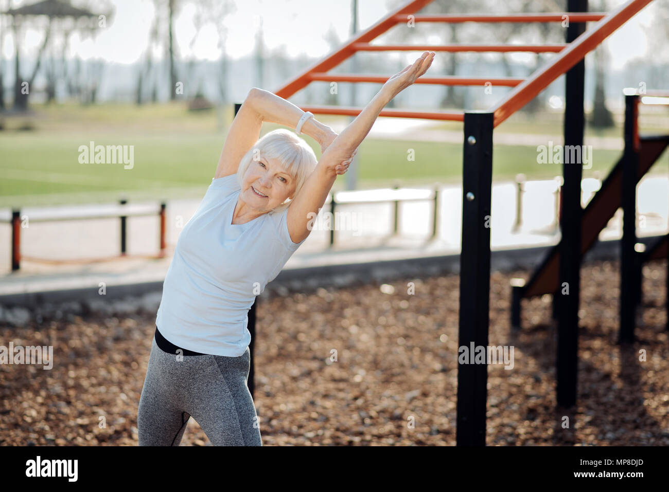 Delighted athletic woman exercising outdoors - Stock Image