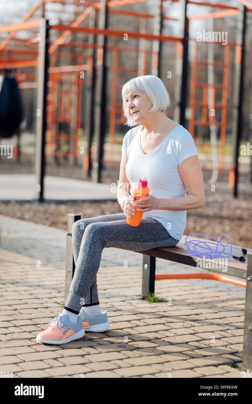 Happy woman relaxing on the bench - Stock Image