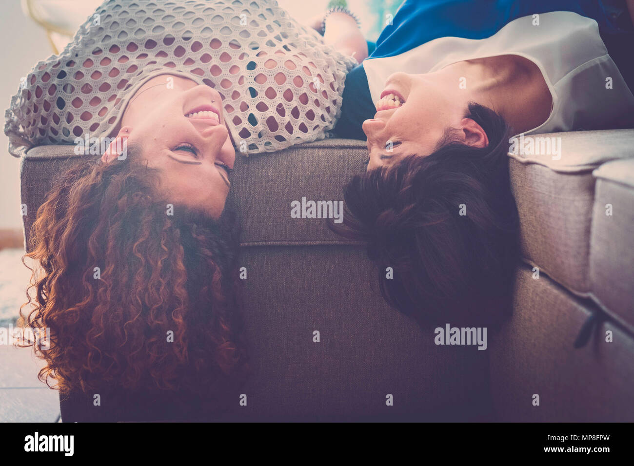 happy time with fun for a couple of young woman laughing and smiling at home lay down on the sofa. best firends forever with secrets concept. - Stock Image