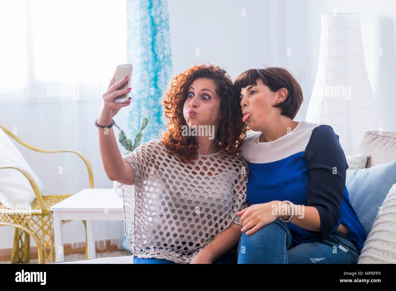 two young women taking pictures with mobile phone at home doing nice and funny expressions. best friends that love to communicate on the net with frie - Stock Image