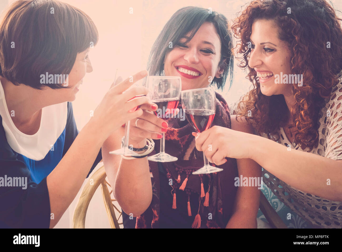 group of people three young women drink some red wine at home to celebrate their friendship. Lot of fun and smilies for a day of party - Stock Image