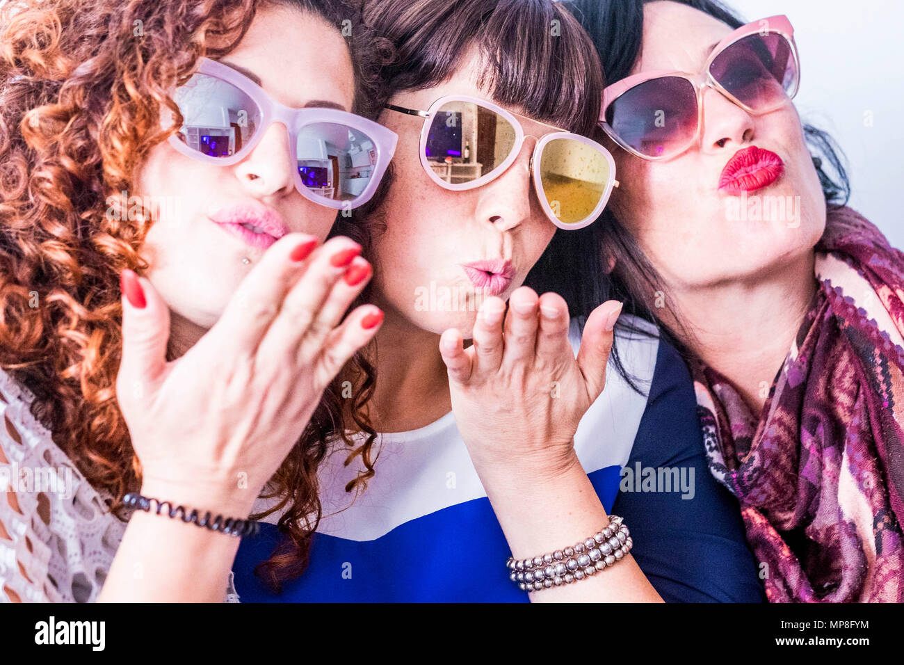 three caucasian young funny crazy woman do a party with colorful sunglasses. sending kiss and having fun together in a real friendship. group people a - Stock Image