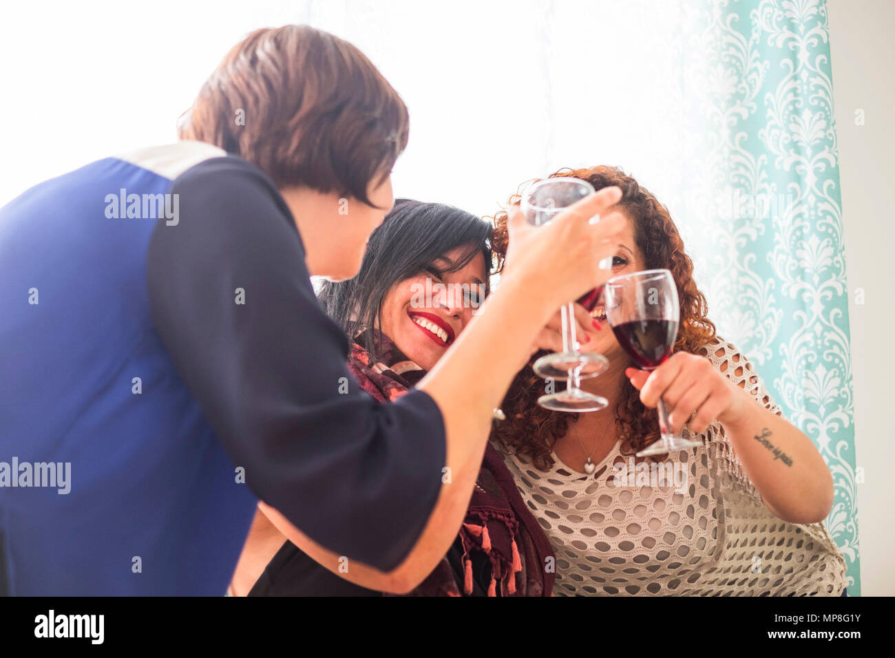 celebration and happiness time for three caucasian young women at home drinking wine together. friendship and party time with backlight from the windo - Stock Image