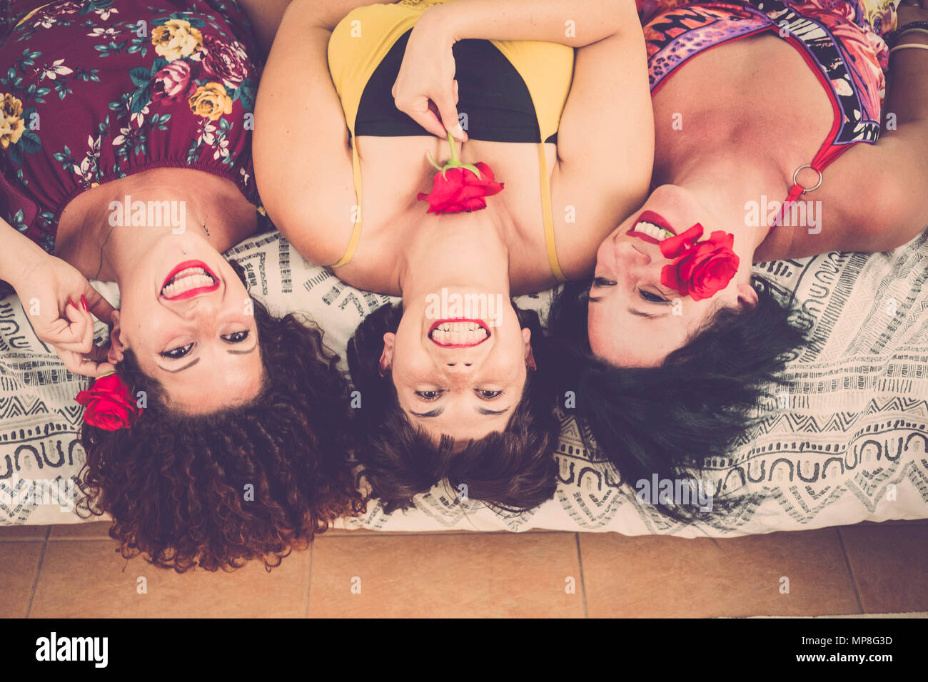 nice and beautiful three caucasian women at home. lay down on the bed looking up with big smile and happiness. playing with roses and red colors lipst - Stock Image