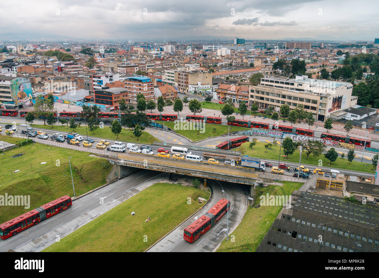 aerial view of early morning rush hour traffic featuring numerous taxis and articulated Transmilenio buses in Colombia's capital, Bogotá - Stock Image