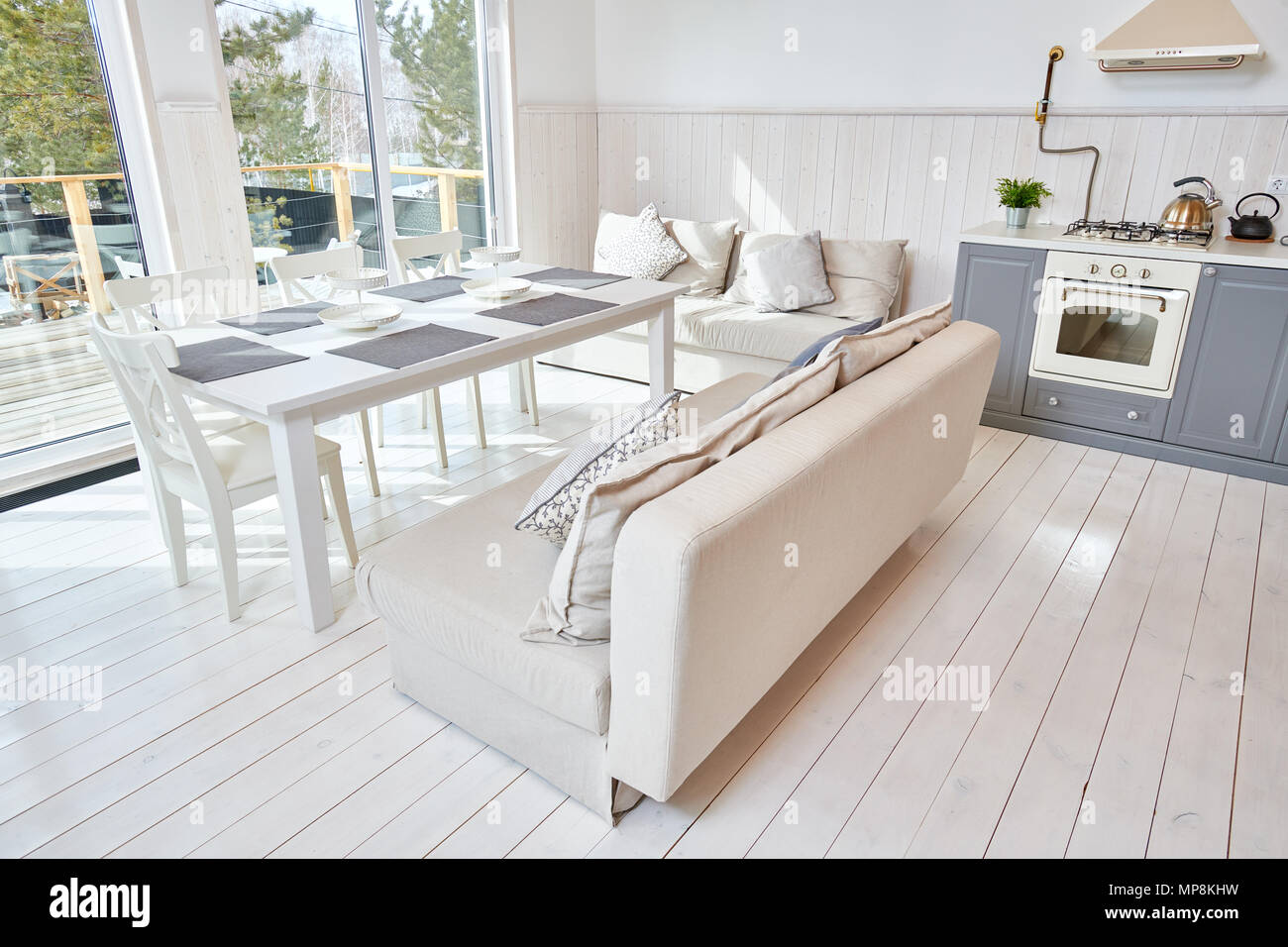 Wide angle shot of open kitchen interior with white furniture and grey counters in minimalistic Scandinavian design lit by sunlight, copy space, nobod - Stock Image