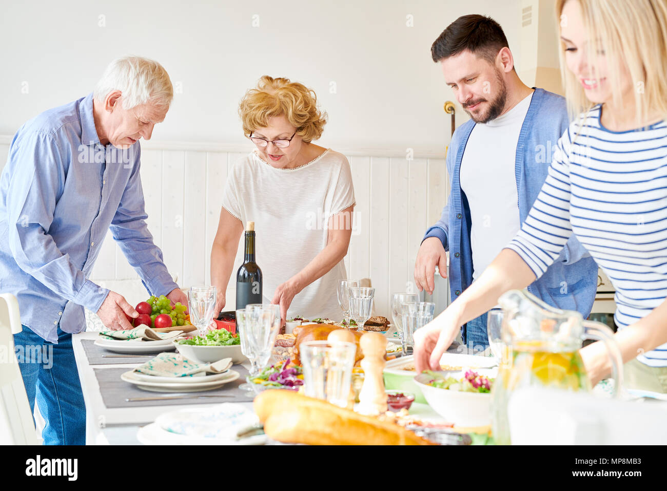 Happy Family Setting Dinner Table - Stock Image