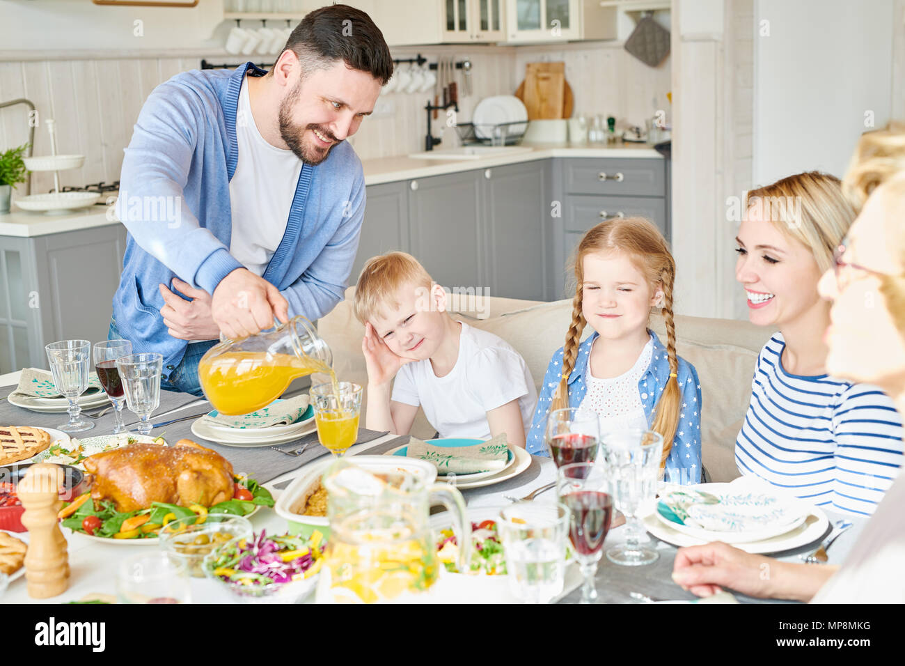 Happy Family at Dinner Table - Stock Image