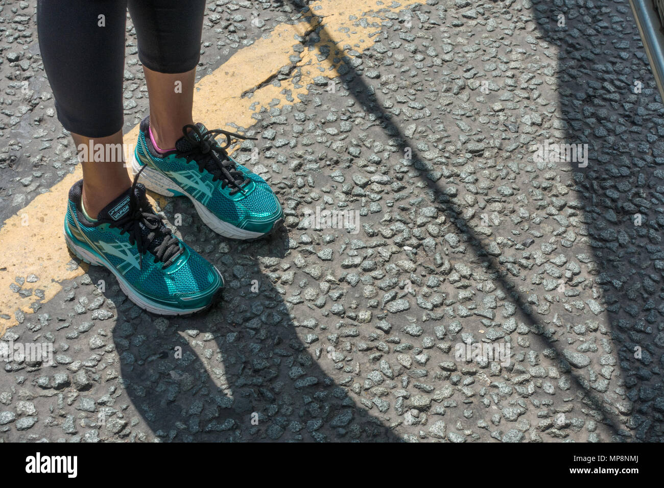 A young women wearing green trainers in preparation to run a 10K race - Stock Image