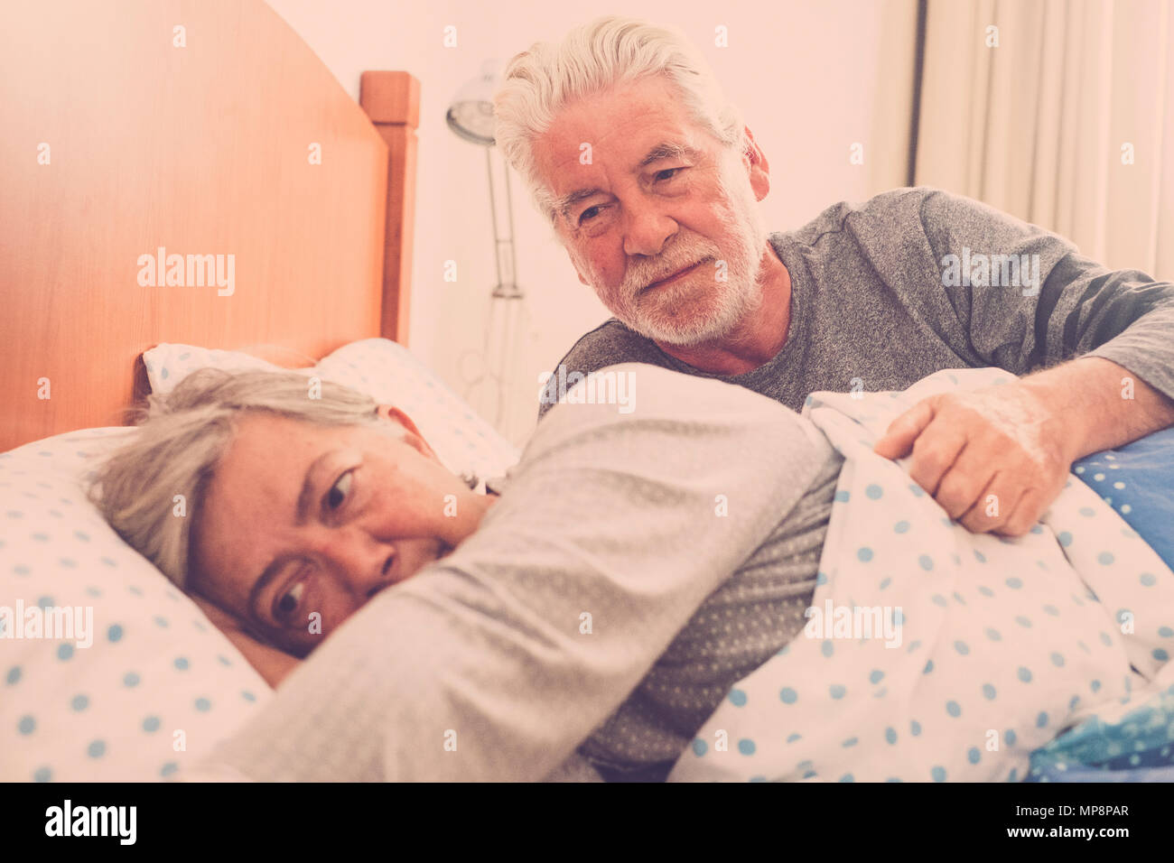adult mature couple lifestyle waking up after the night. bedroom scene with window natural light. love forever together and nice life concept. white h - Stock Image