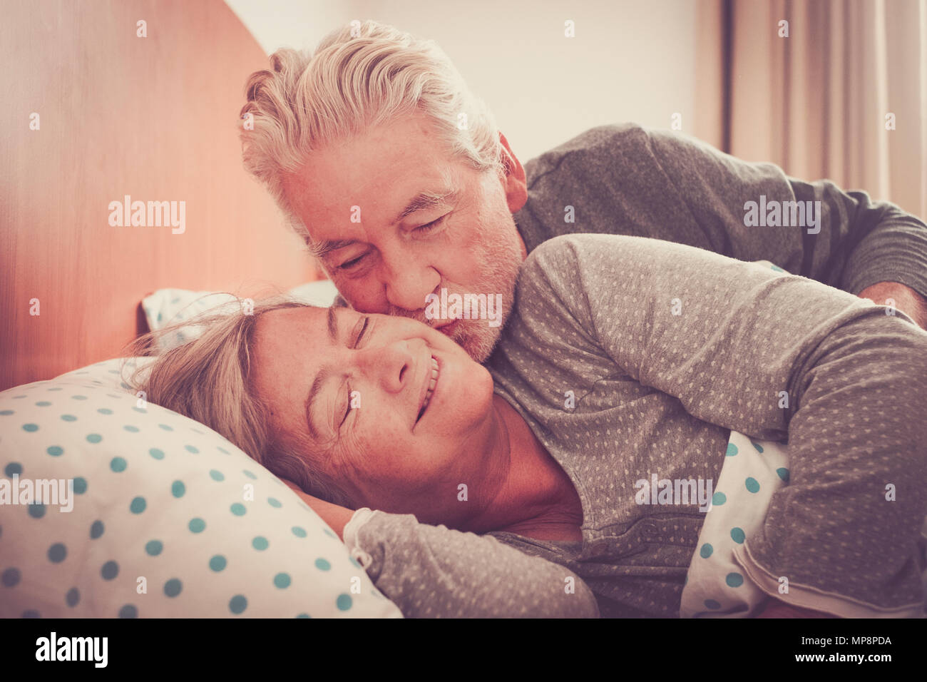 Couple of senior man and woman waking up and smiling with a hug while are in the bed at home. Vintage filter and light in the back. The man kiss the w - Stock Image