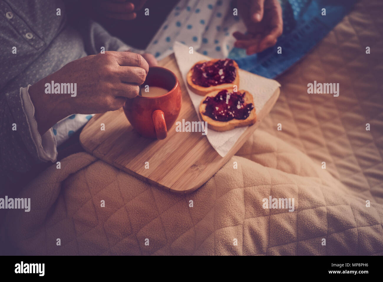 bedroom brekfast colose up at home. senior couple eat marmelade and milk and then wake up and start a new nice day together. vintage filter and beauti Stock Photo