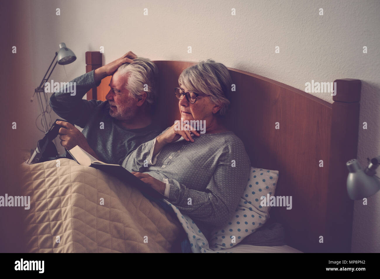 caucasian senior adult couple stay and rest on the bed. the wman read a book the man play with goggled headset technology. beautiful model and light f Stock Photo