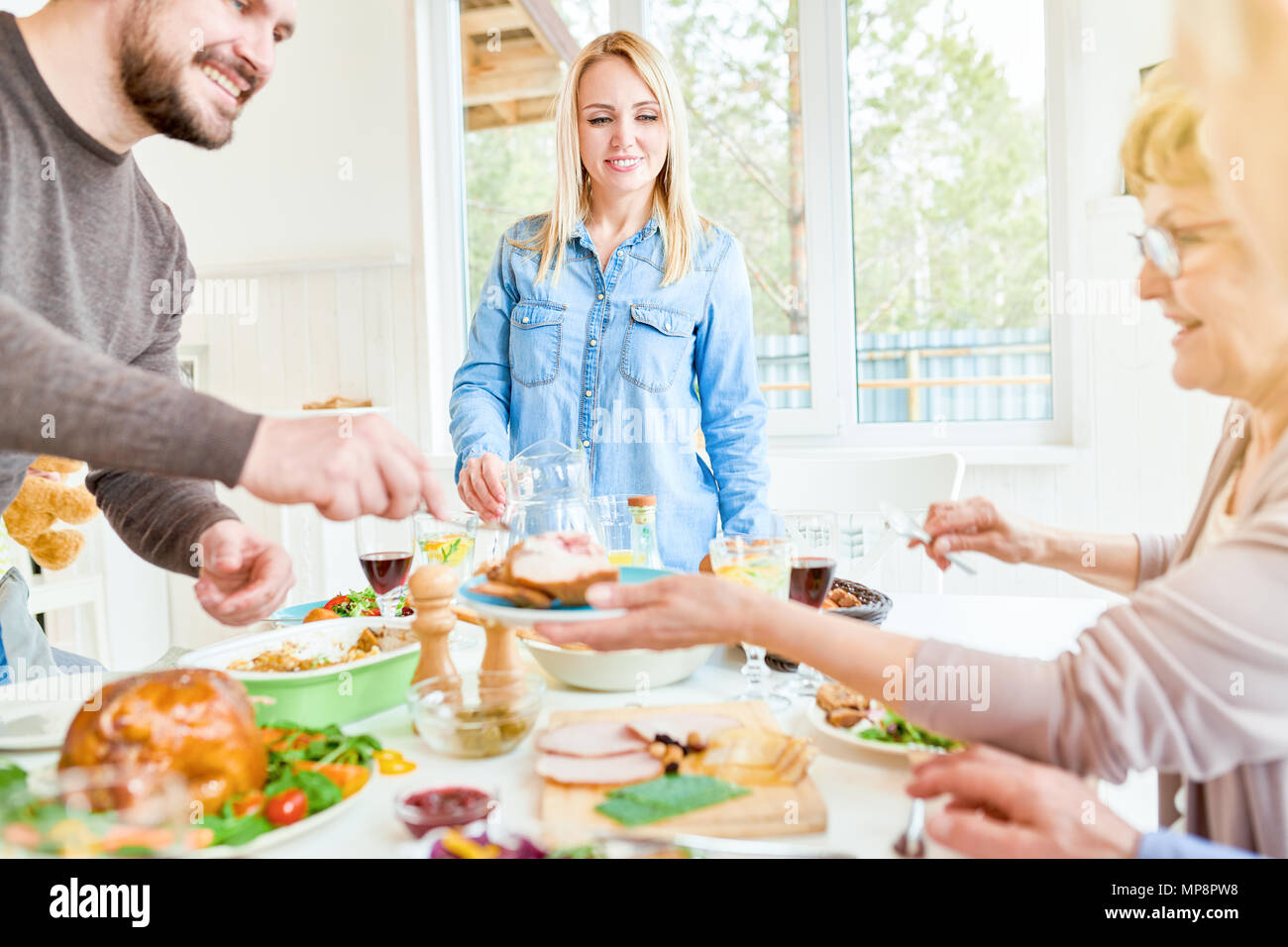 Young Woman Hosting Family Dinner - Stock Image
