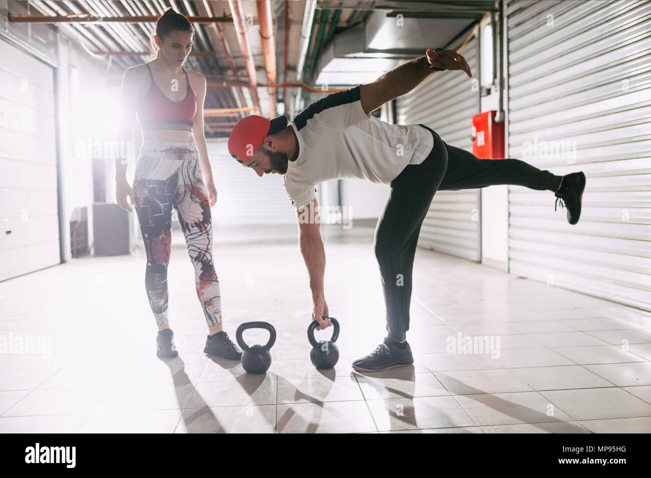 Young muscular woman doing strength exercise with kettlebell on a