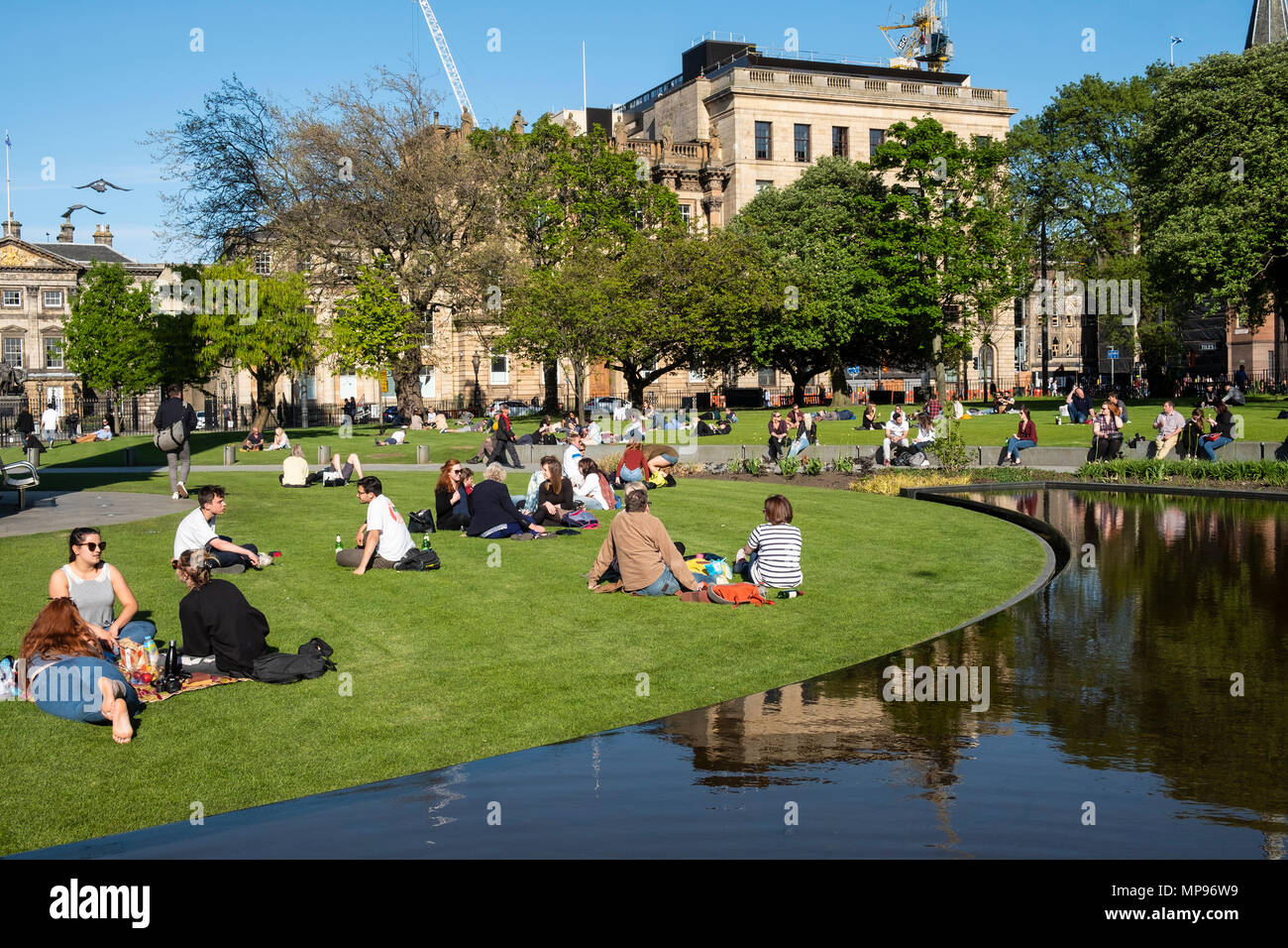 People sitting on grass in St Andrews Square in warm, sunny weather in Edinburgh, Scotland, United Kingdom,UK - Stock Image