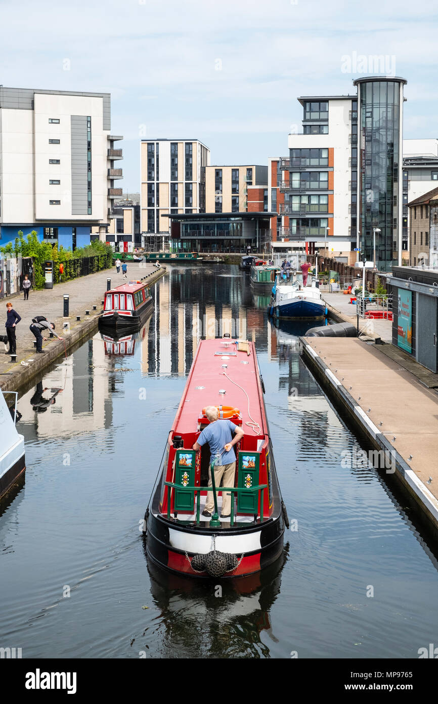 View of Union Canal at Lochrin Basin with narrow boat sailing to mooring at Fountainbridge in Edinburgh, Scotland, United Kingdom, UK - Stock Image