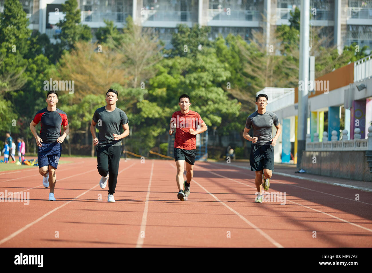 young asian adult athletes running training on track, front view. - Stock Image