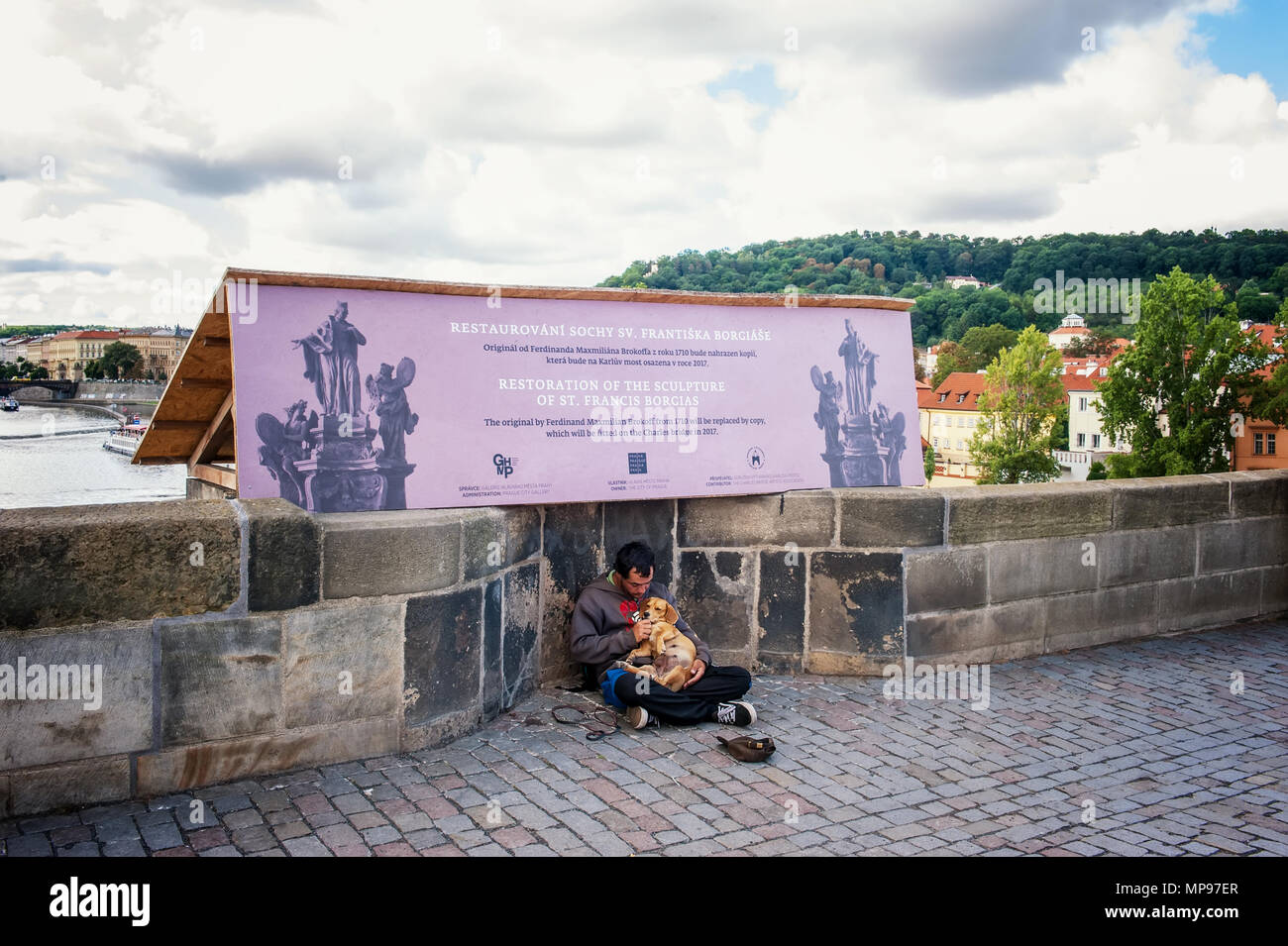 Prague 13.08.2013. A homeless young man with a big black dog on the street asking passersby for money. The horizontal frame. - Stock Image