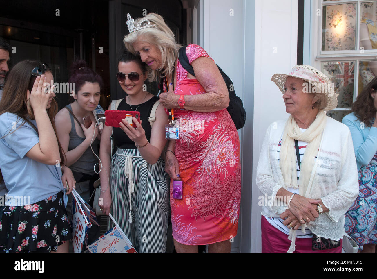 People in crowd with mobile devises iphone  smartphone, smartphones, watching Prince Harry Meghan Markle Royal Wedding on on mobile i phone 2018  HOMER SYKES Stock Photo