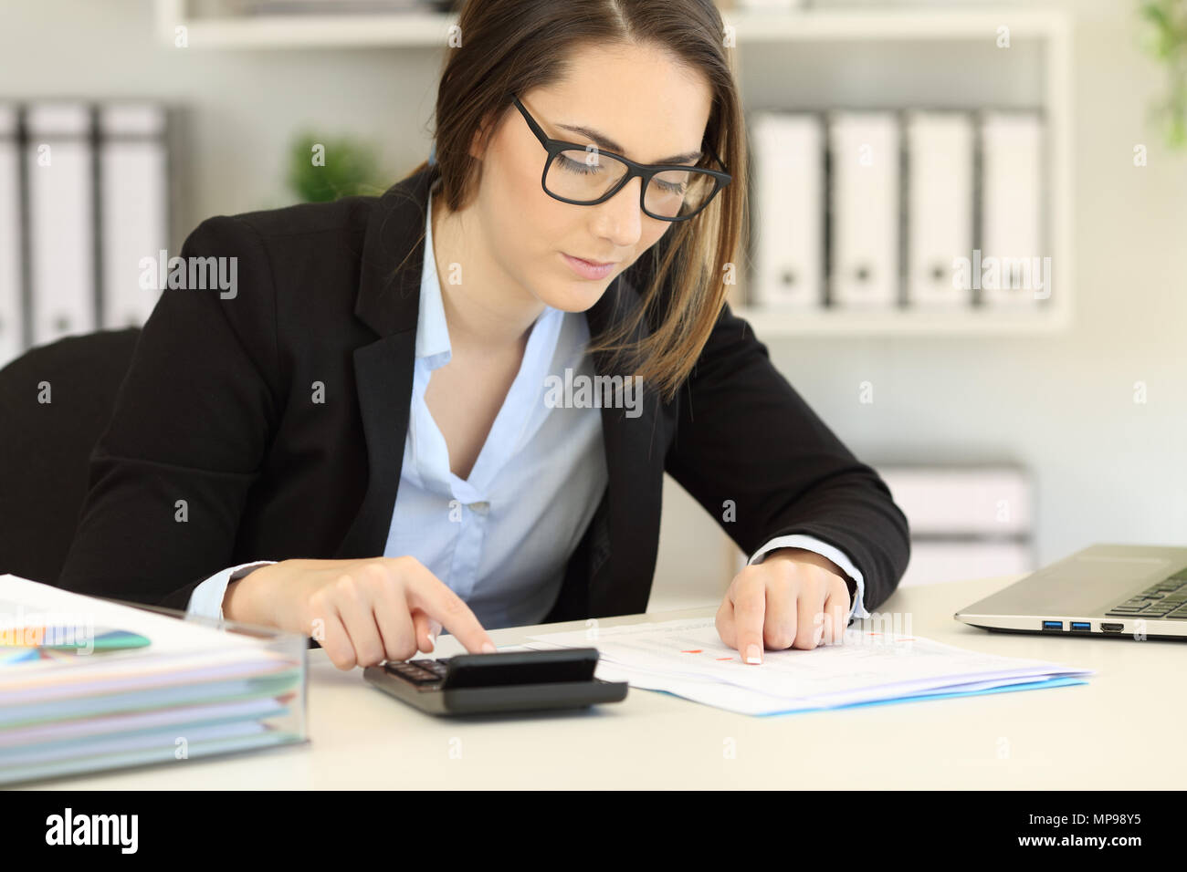 Serious bookkeeper calculating expenses using a calculator - Stock Image