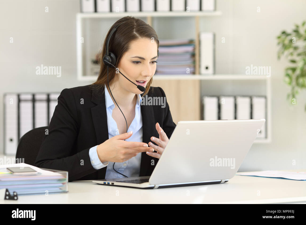 Telemarketer talking on-line having a video call with a laptop at office Stock Photo