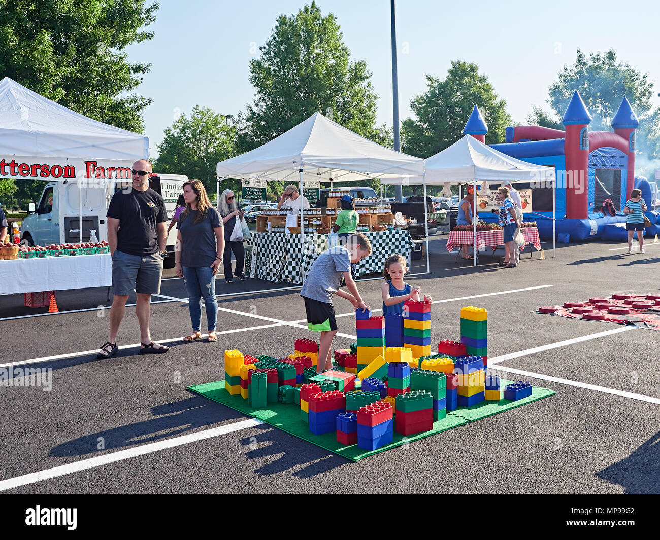 Boy and girl children play or playing with giant Lego blocks at a family fun farmer's market with their parents watching in Montgomery Alabama, USA. - Stock Image