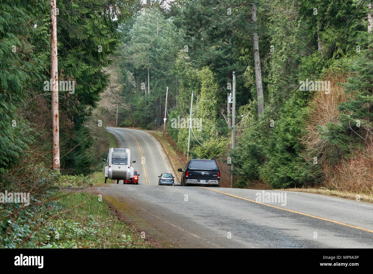 On a rural road through the forest, three cars travel down a hill ...