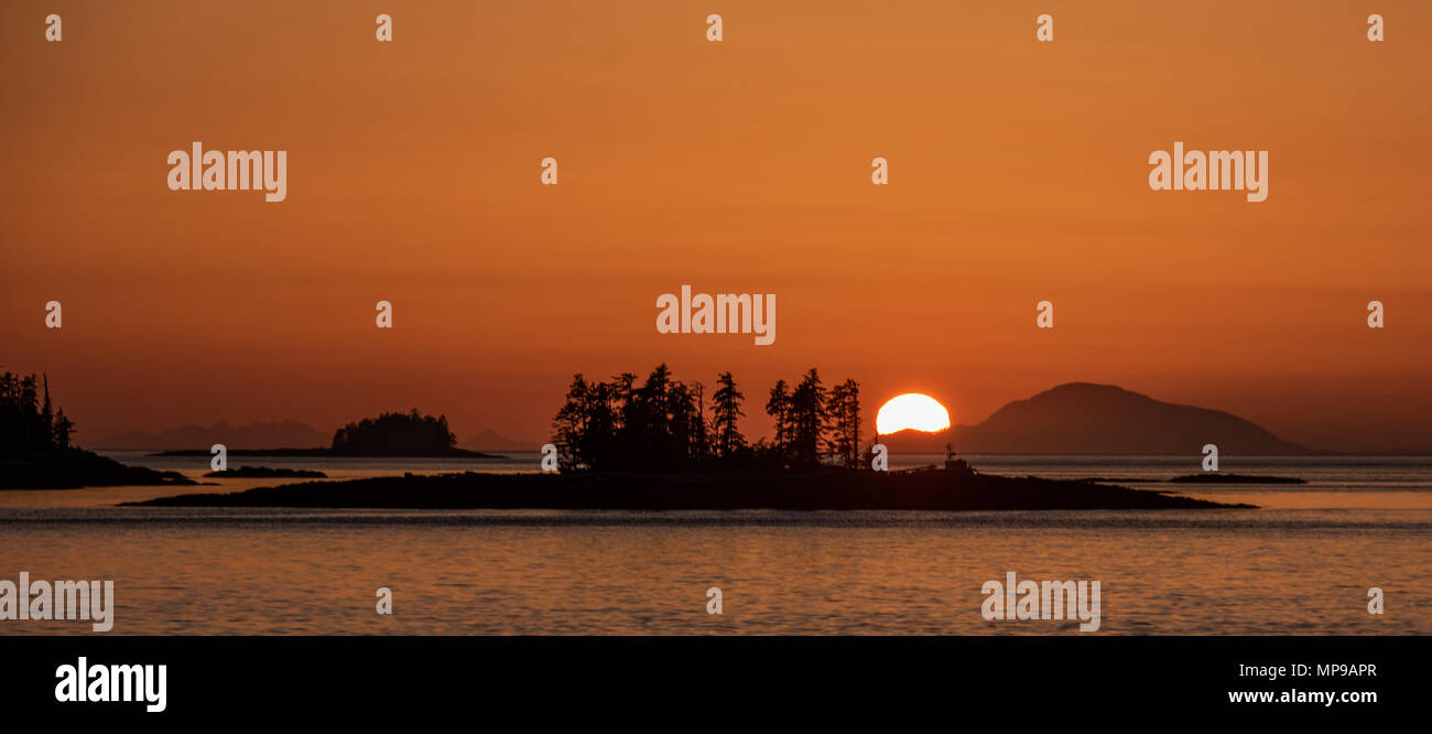 The sun sets while transiting Chatam Strait in the Inside Passage - Stock Image