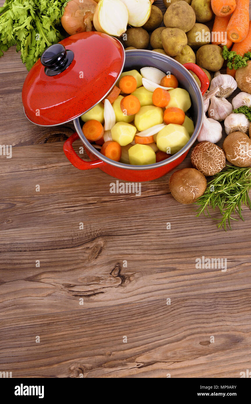 Red casserole pot with organic vegetables and herbs on a wooden table with copy space. - Stock Image